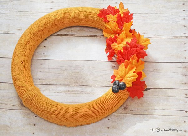 Give a pool noodle a warm makeover with this cozy Fall wreath idea. {OneCreativeMommy.com} Pool noodle wreath | Sweater makeover