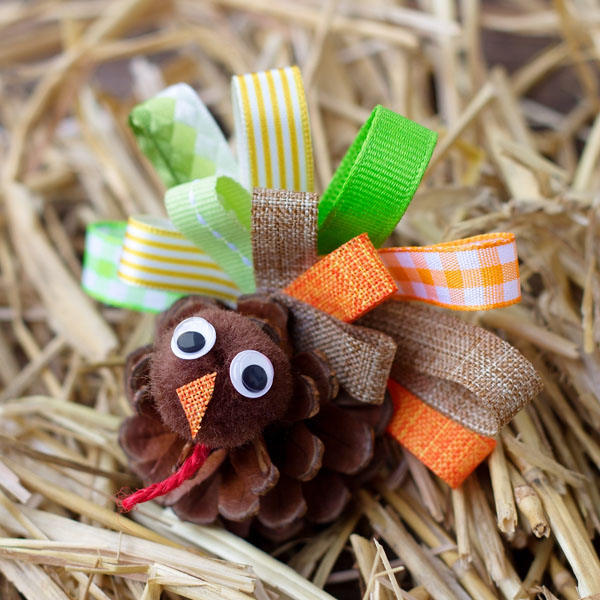 Scrap Ribbon Pinecone Turkeys from Fireflies and Mudpies | Featured in the Ultimate Turkey Crafts for Kids Roundup {OneCreativeMommy.com}