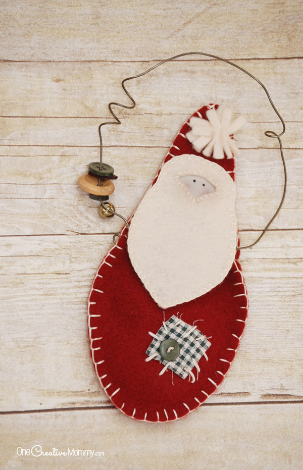 Rustic Santa Claus Door Hangers make perfect gifts for teachers, friends and neighbors. They're easy to make, and they look so darn cute! {OneCreativeMommy.com} Christmas Craft Tutorial #santaclaus #christmascraft #christmasdecor #felt #giftidea #doorhanger